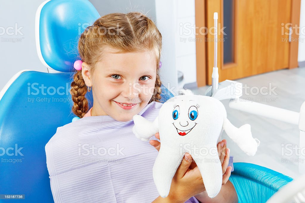 Cheerful child holding a toy tooth stock photo