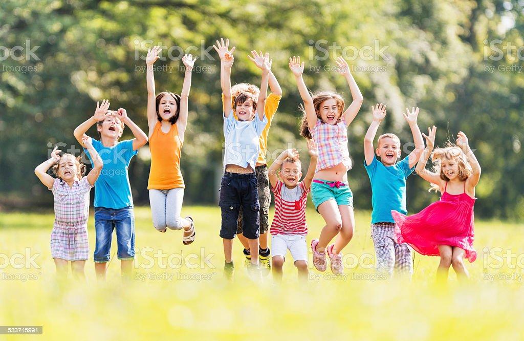 Cheerful children jumping in nature. stock photo