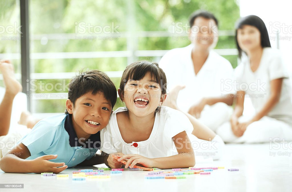 Cheerful children playing with a puzzle at home. stock photo