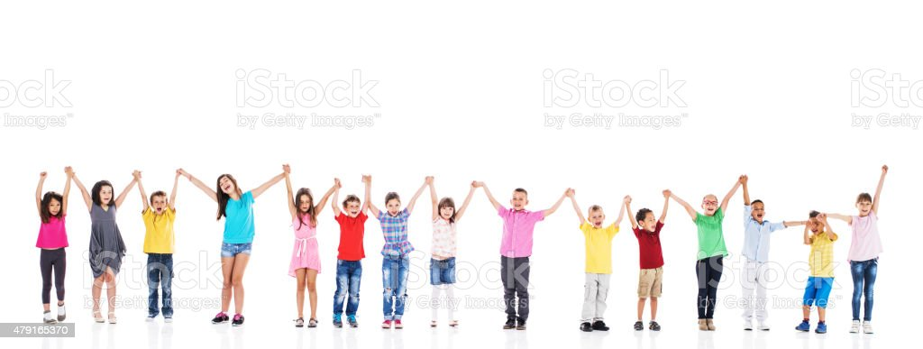 Cheerful children standing in a line and holding hands. stock photo
