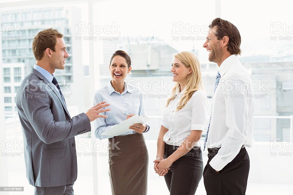 Cheerful colleagues in discussion at office stock photo