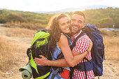 Cheerful couple backpackers embracing