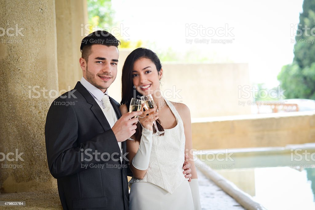 cheerful couple bride and groom cheering with champagne on wedding stock photo