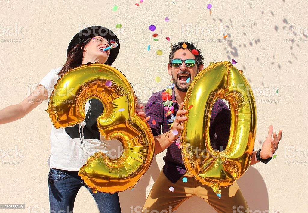 Cheerful couple celebrates a thirty years birthday stock photo