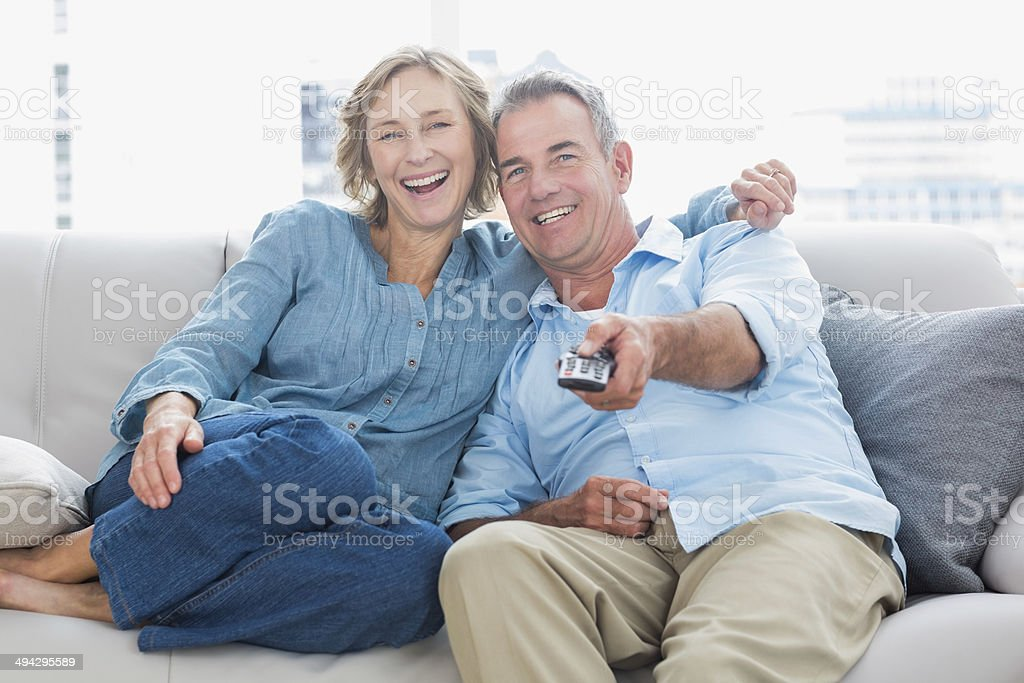 Cheerful couple cuddling and sitting on the couch watching tv stock photo