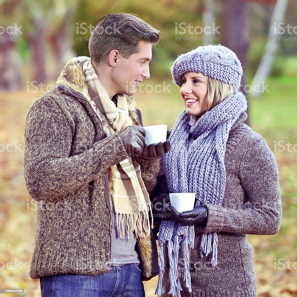 Cheerful couple drinking coffee outdoors in an autumn day royalty-free stock photo