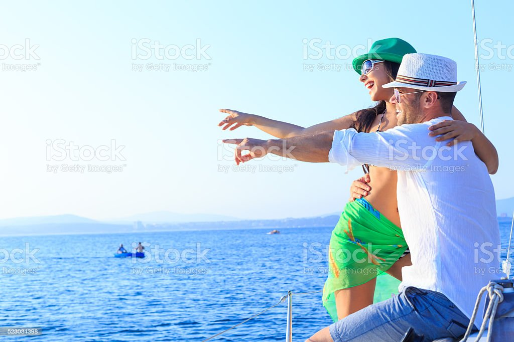 Cheerful couple enjoying sailboat trip stock photo