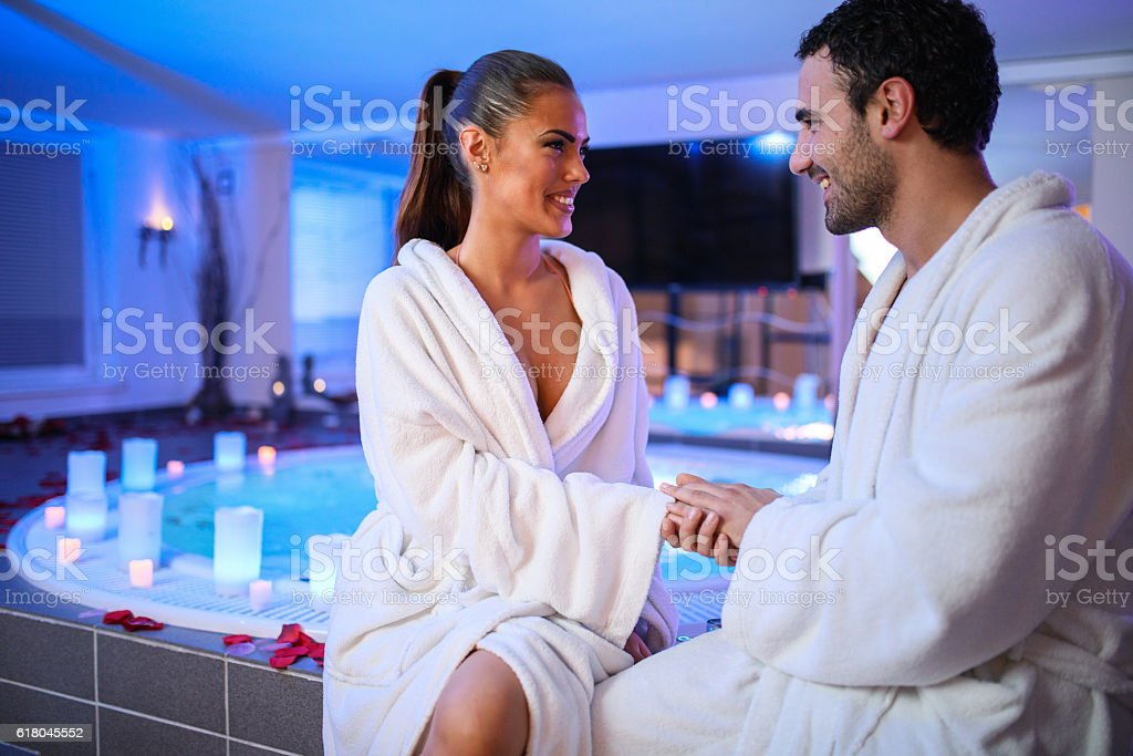 Cheerful couple flirting while sitting outside of hot tub. stock photo