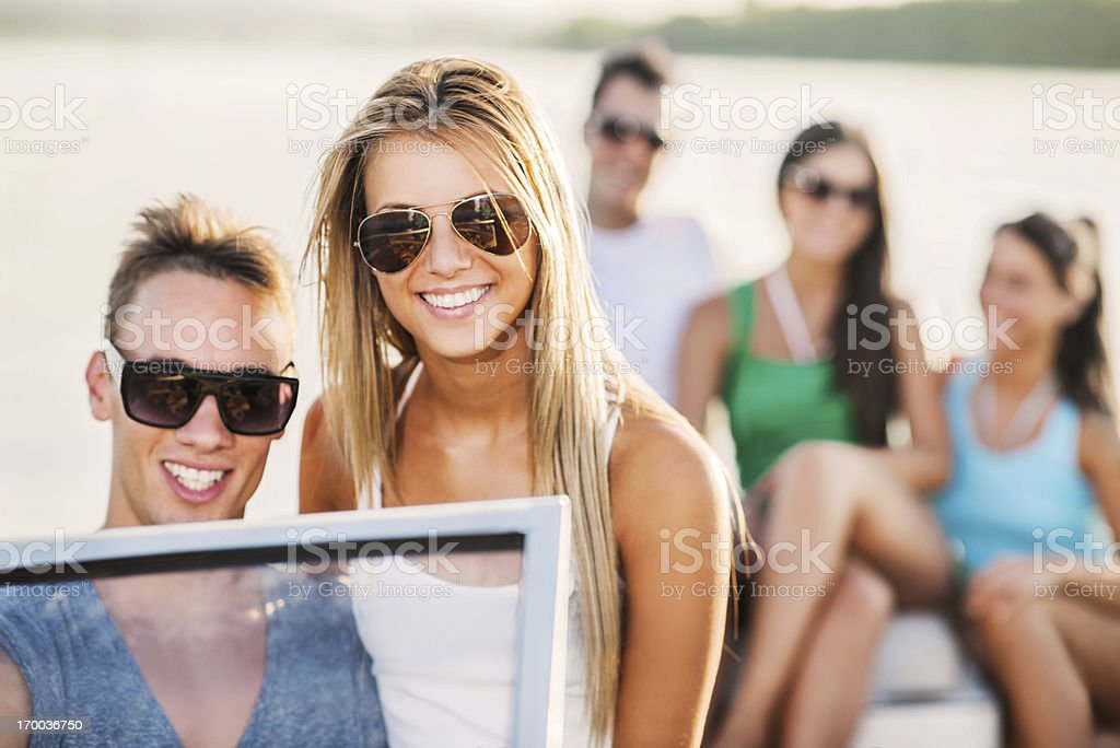 Cheerful couple giving their friends a speedboat ride. stock photo