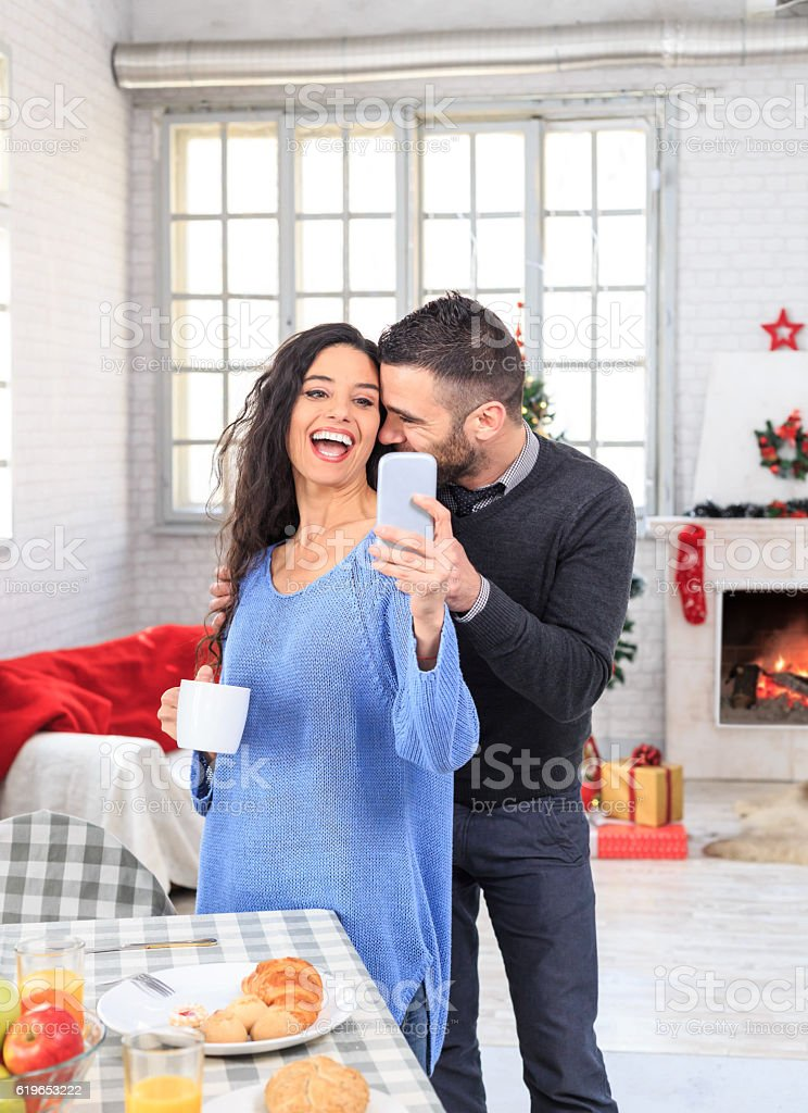 Cheerful couple having breakfast at home and making selfie stock photo