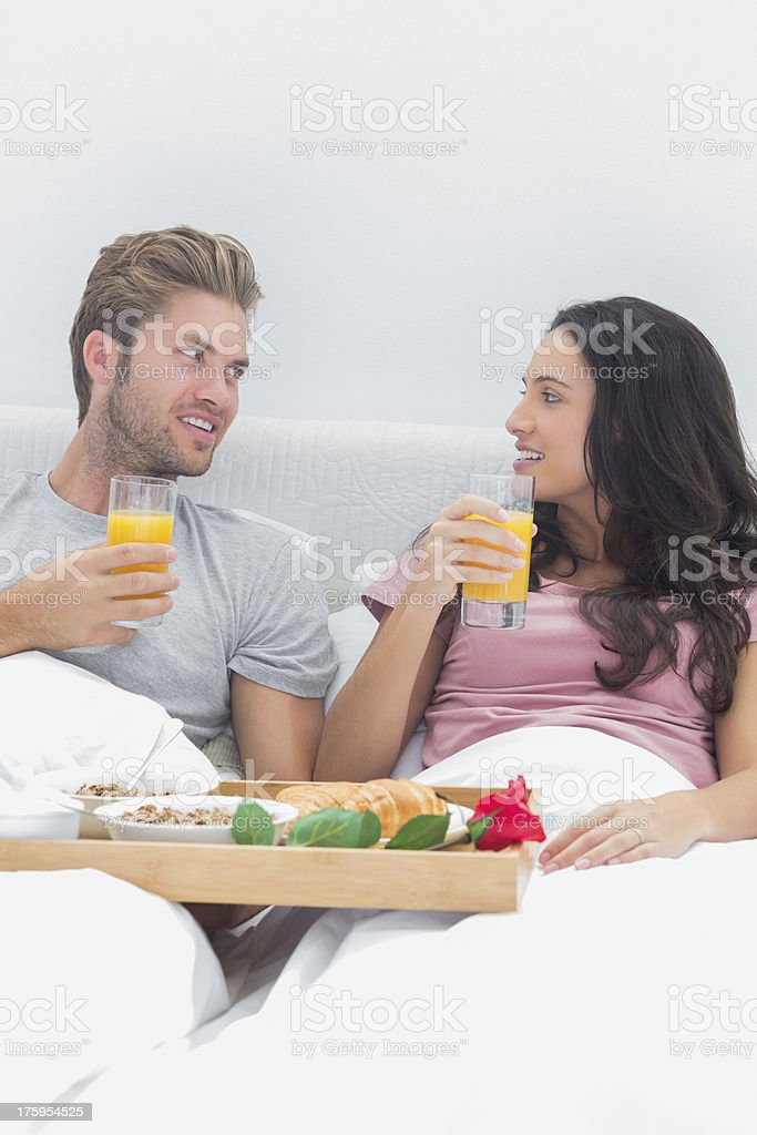 Cheerful couple having breakfast in bed royalty-free stock photo