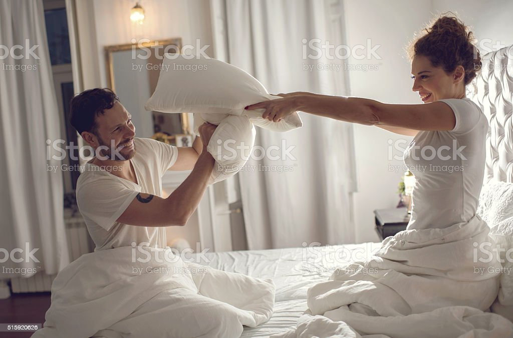 Cheerful couple having fun in bedroom while fighting with pillows. stock photo