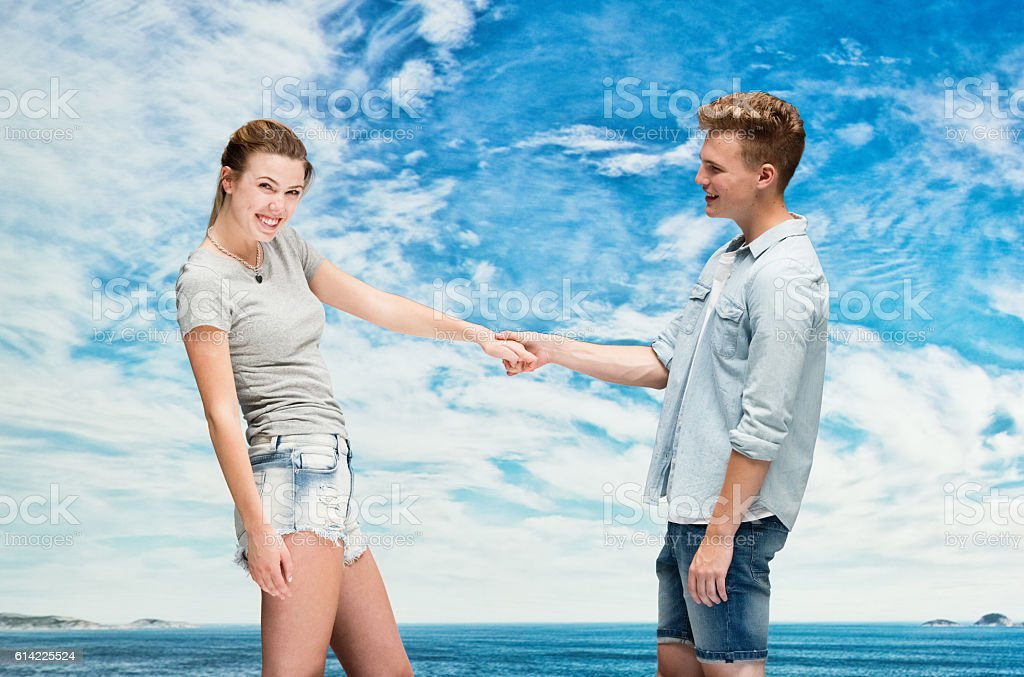 Cheerful couple holding hands outdoors stock photo