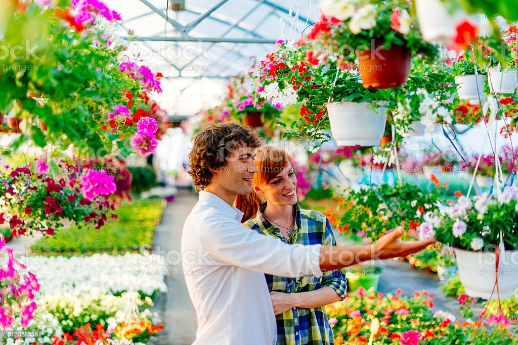 Cheerful couple in flower shop stock photo
