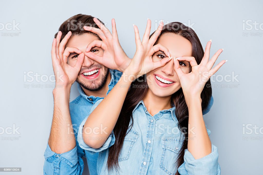 Cheerful couple in love having fun with fingers near eyes stock photo