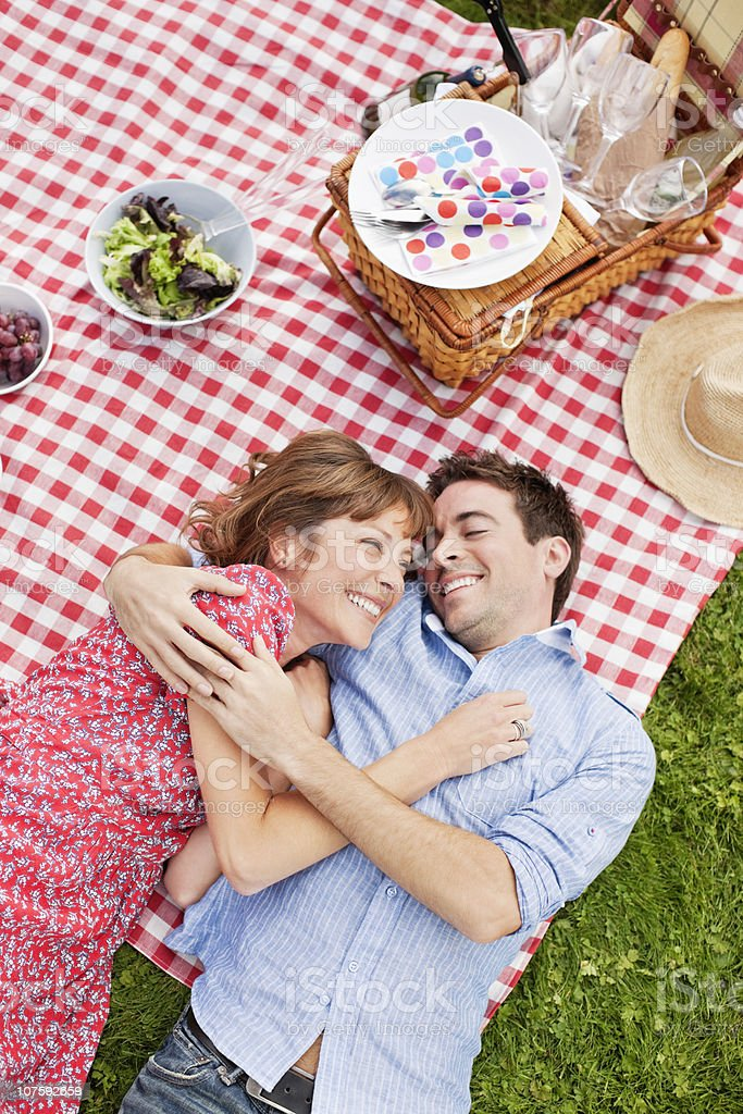 Cheerful couple lying on picnic blanket with arm around, directly above royalty-free stock photo