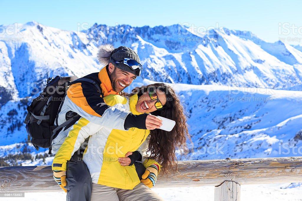 Cheerful couple making selfie in ski resort stock photo