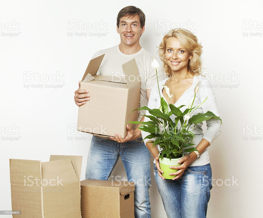 Cheerful couple moving into a new home and packing boxes. royalty-free stock photo