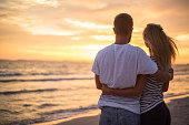 Cheerful couple on beach watching sunset