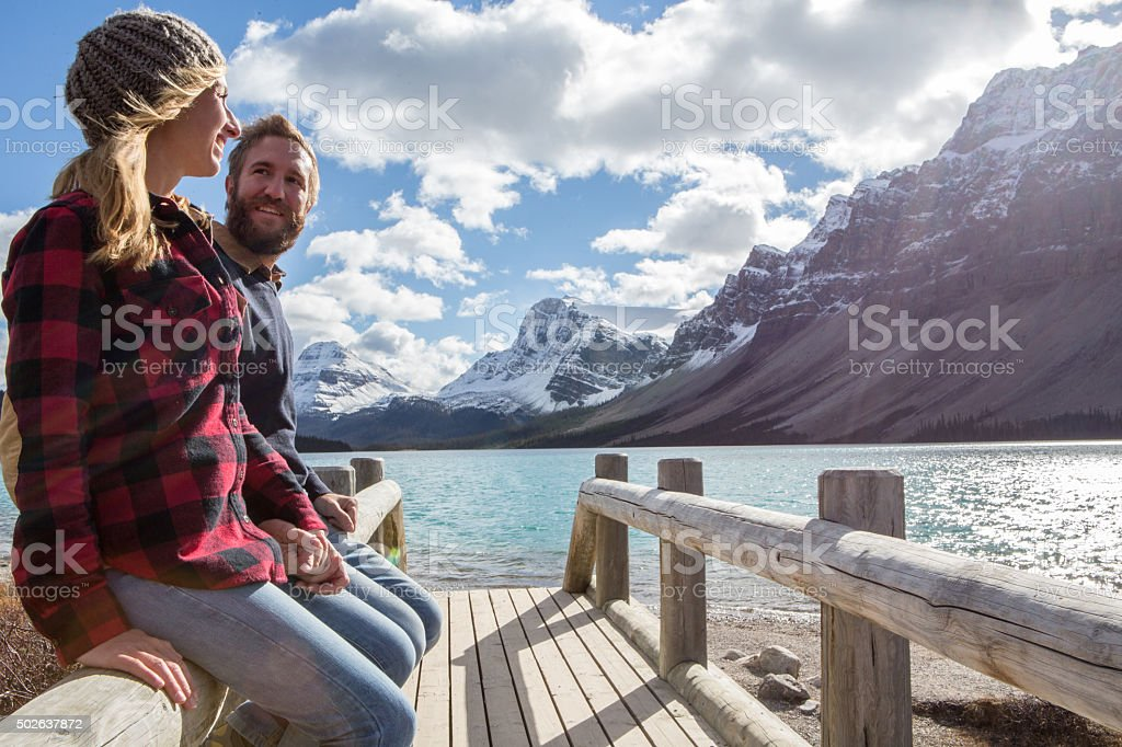 Cheerful couple on log bridge admiring landscape stock photo