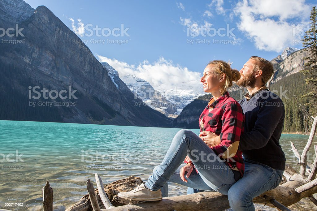 Cheerful couple on log tree by the lake stock photo