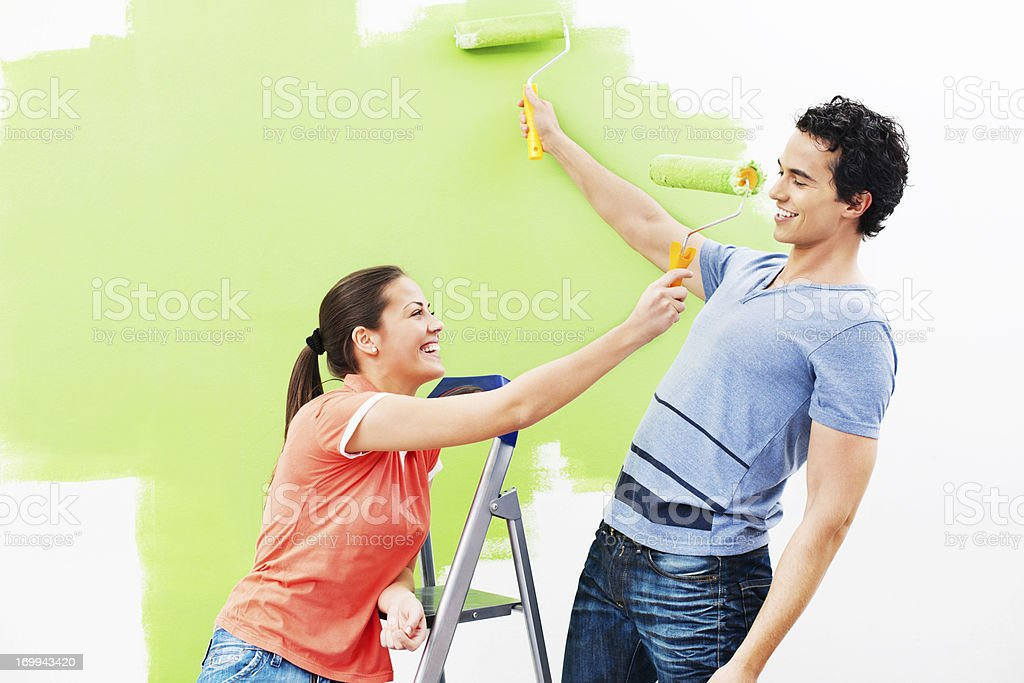 Cheerful couple playing while painting the wall green royalty-free stock photo