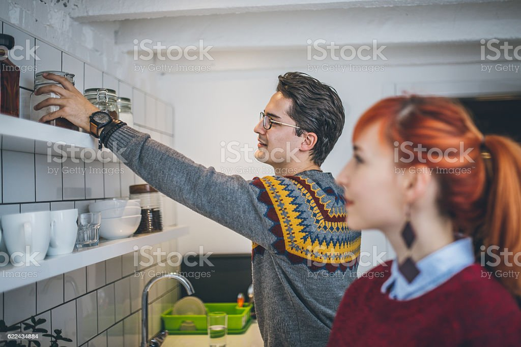 Cheerful couple preparing coffee in the kitchen stock photo