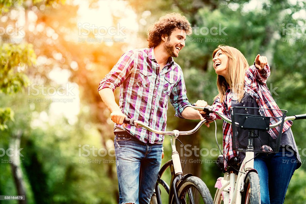 Cheerful couple pushing bicycles and walking. stock photo