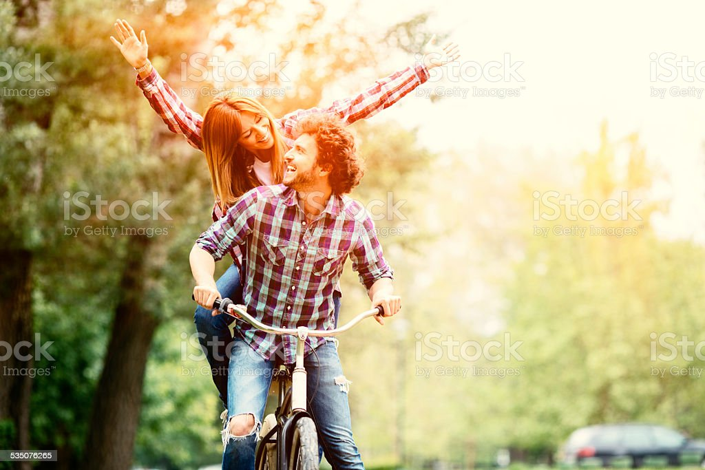 Cheerful Couple Riding Bicycle Together. stock photo