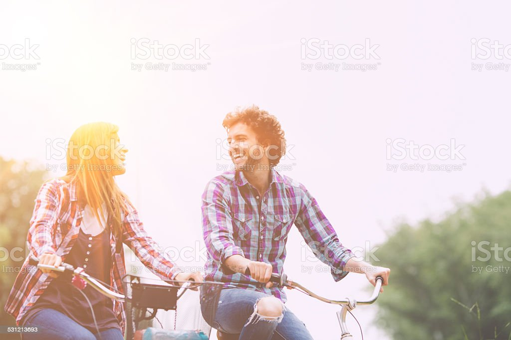 Cheerful Couple Riding Bicycles Together. stock photo