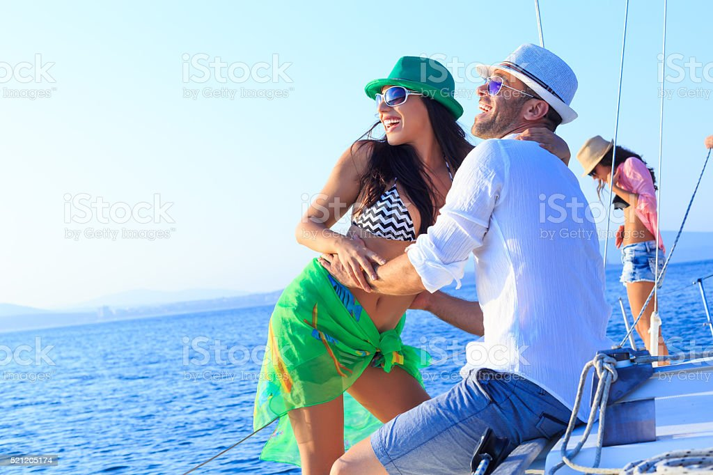 Cheerful couple sailing together with friends stock photo