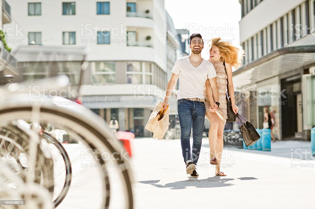 cheerful couple shopping and walking by the street stock photo