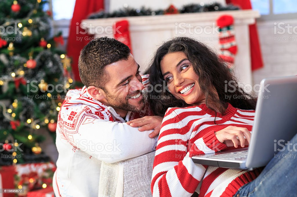 Cheerful couple sitting at home and using laptop stock photo