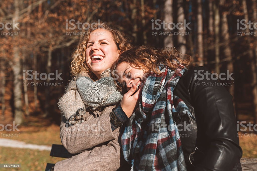 Cheerful couple sitting on a bench stock photo