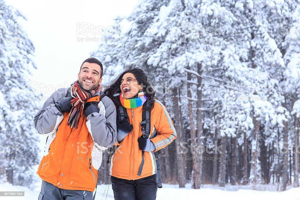 Cheerful couple tourists hiking in snow forest stock photo