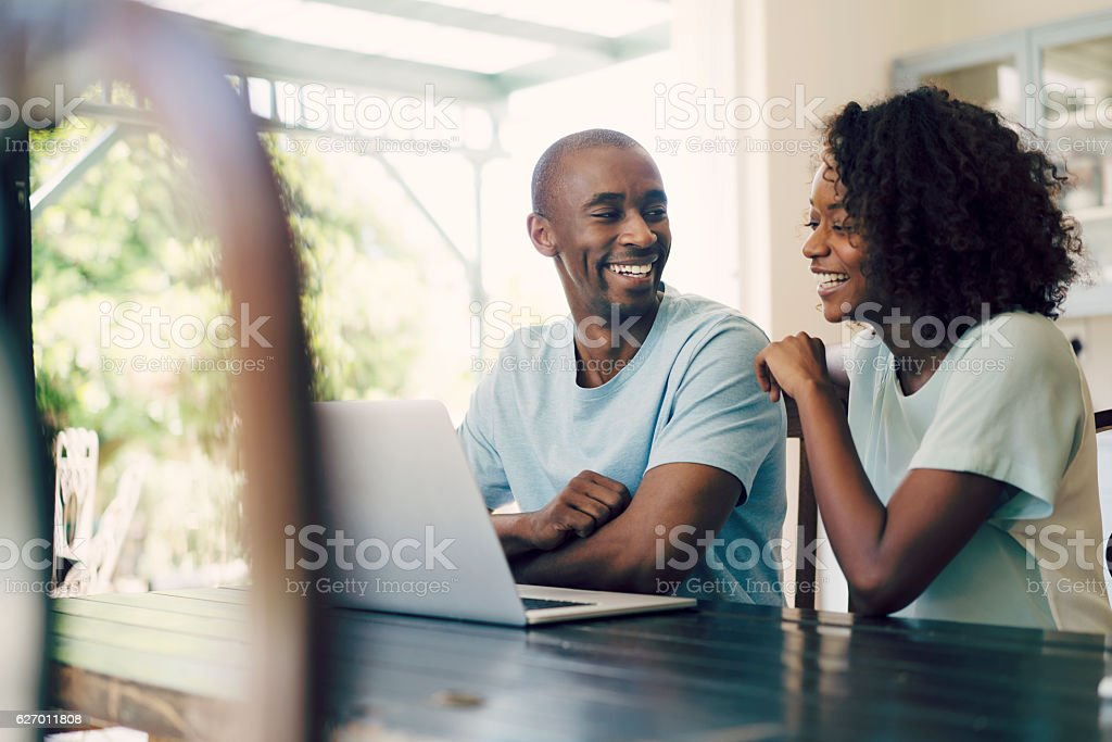 Cheerful couple using laptop at home stock photo