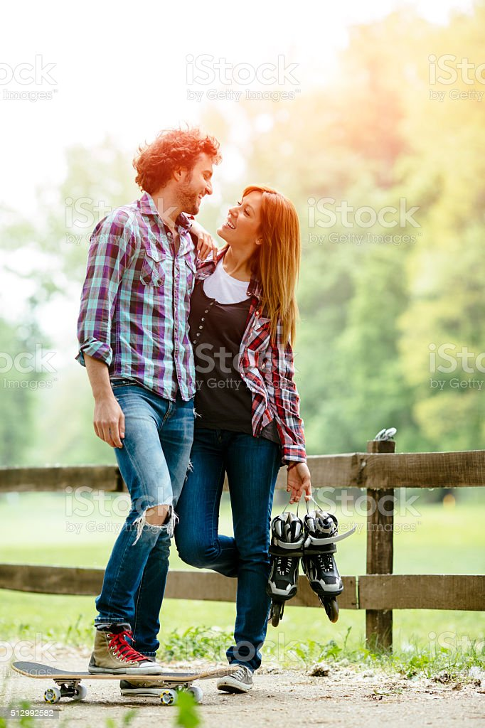 Cheerful Couple Walking With Skateboard and Roller Skates Outdoors. stock photo