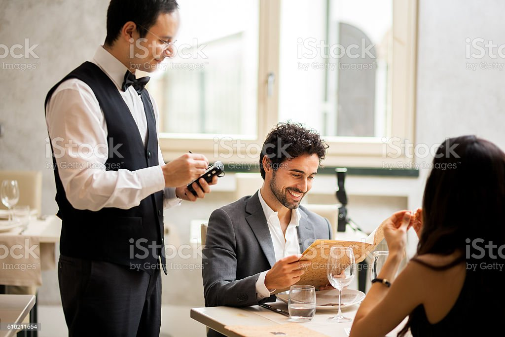 Cheerful couple with menu in a restaurant making order stock photo