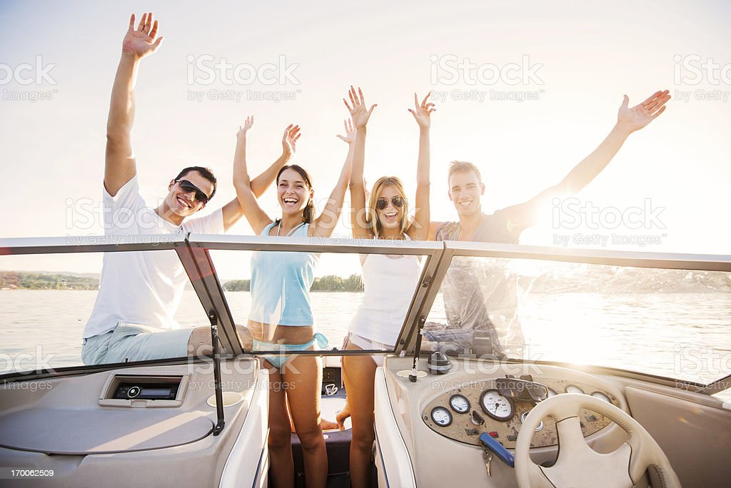 Cheerful couples enjoying on a speedboat ride. stock photo