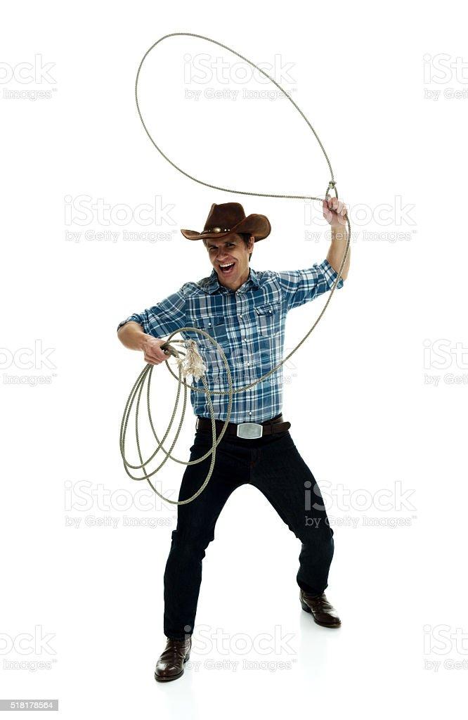 Cheerful cowboy lassoing stock photo