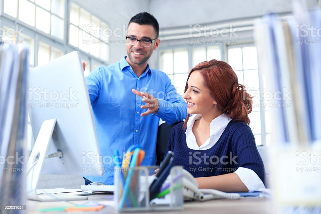 Cheerful coworkers working on computer in the office stock photo