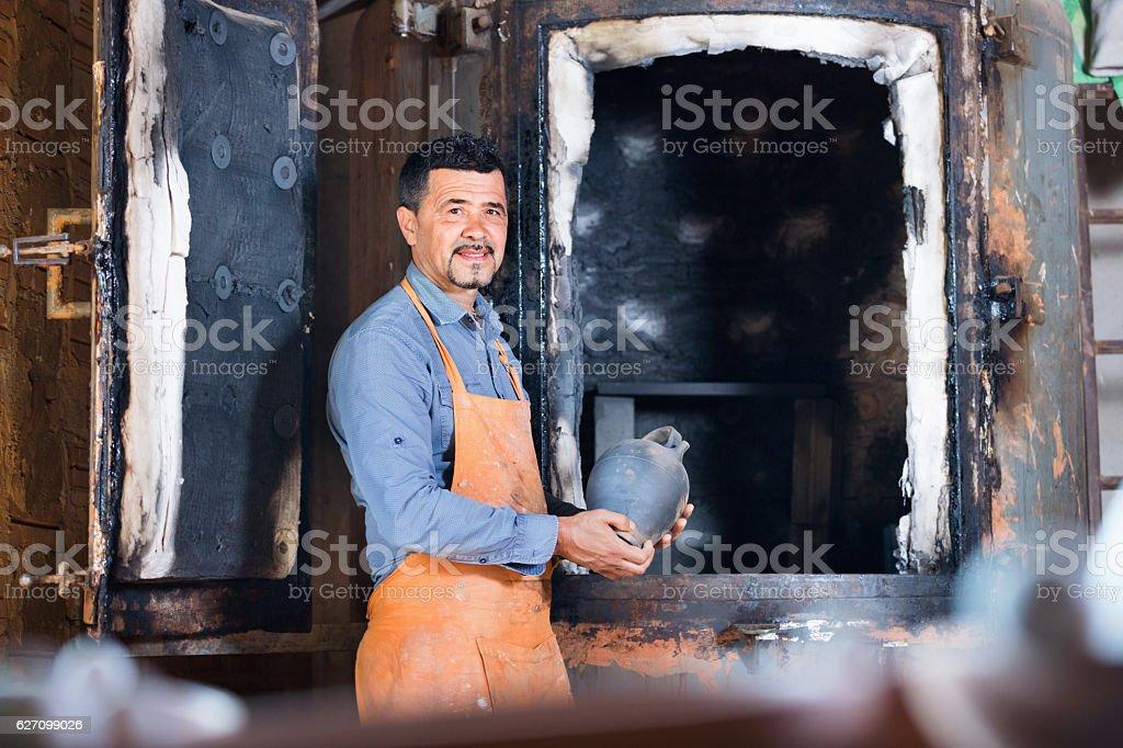 Cheerful craftsman carrying fresh baked black glazed vessel stock photo
