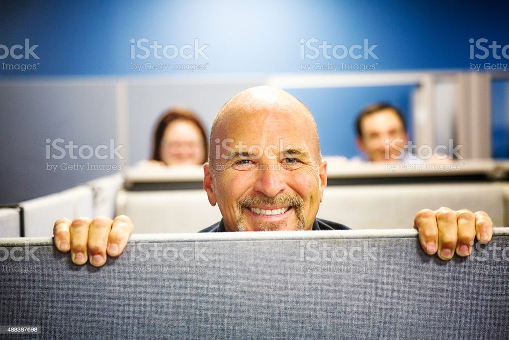 Cheerful cubicle worker portrait peeking over wall smiling stock photo