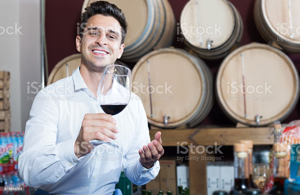 Cheerful customer holding glass of red wine and tasting stock photo