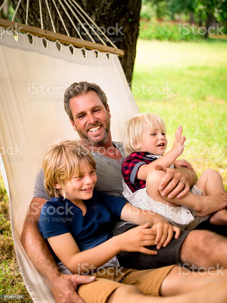 Cheerful dad hugging his two sons on hammock outside stock photo