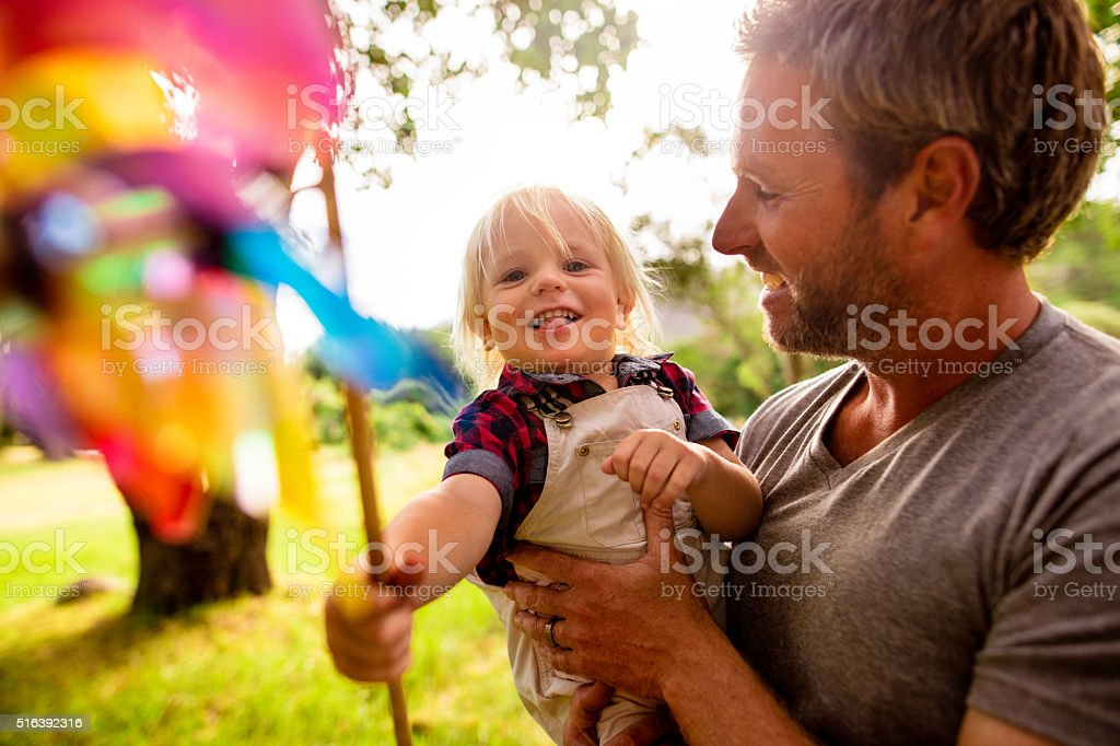 Cheerful dad take his laughing son in his arms outside stock photo