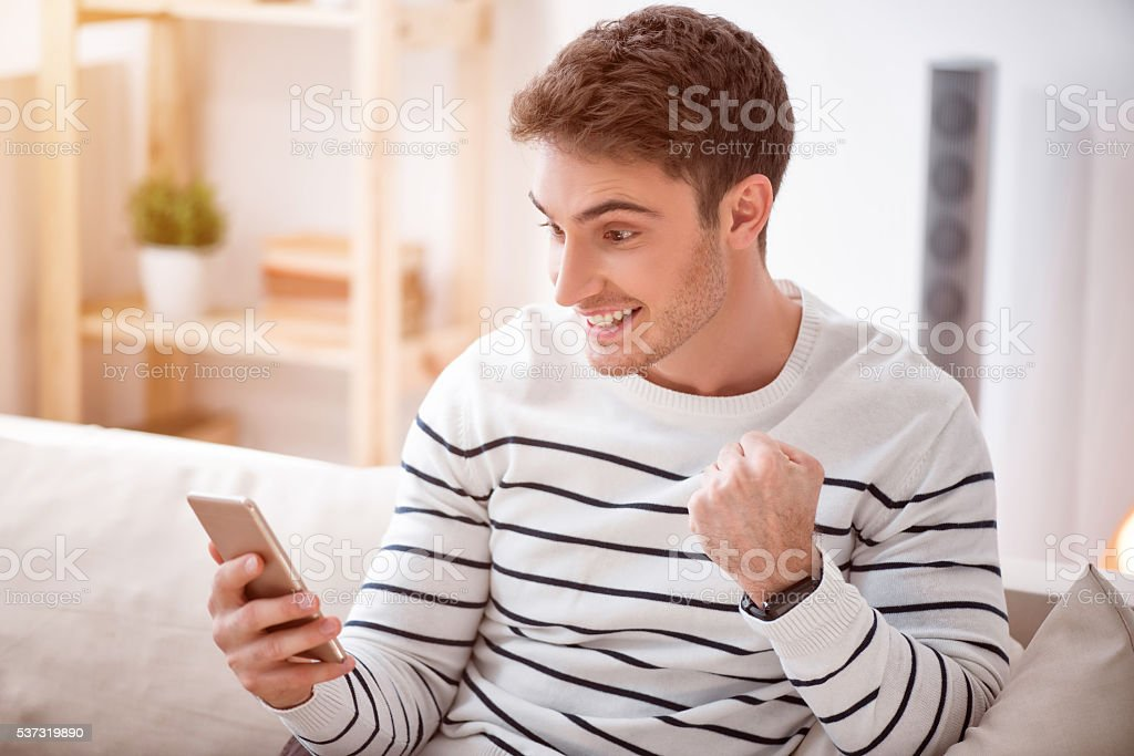 Cheerful delighted  man sitting on the sofa stock photo
