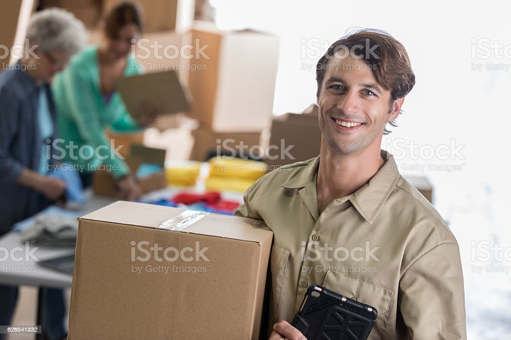 Cheerful delivery man delivers package to small business owners stock photo