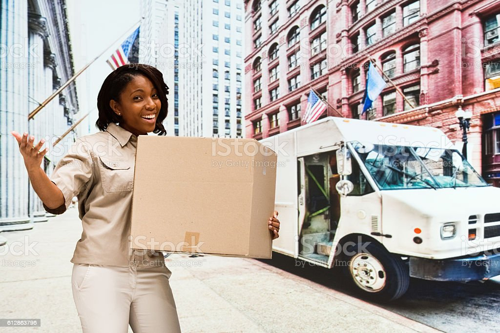 Cheerful delivery person gesturing outdoors stock photo