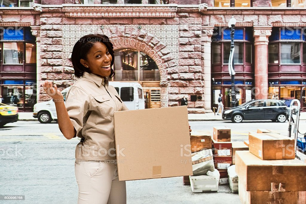 Cheerful delivery person presenting outdoors stock photo